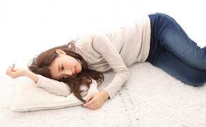 つらそうに横たわる女性